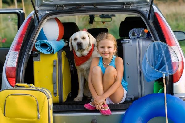 Maedchen fertig fuer Urlaub in den Bergen mit Hund