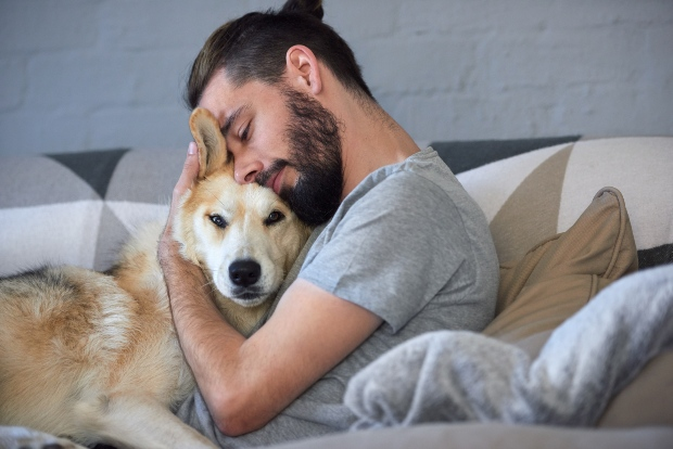 Hund mit Herrchen beim Kuscheln