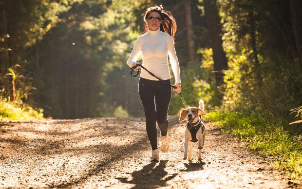 Frau joggt mit Hund an der Leine