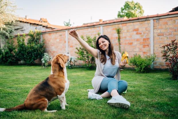 Fra gibt Hund im Garten einen Snack