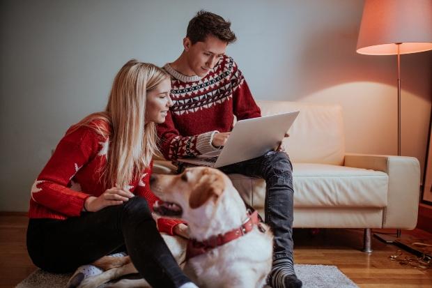 Hund liegt bei Herrchen und Frauchen - Frohe Hundeweihnachten