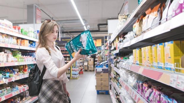 Junge Frau liest Zutatenliste von Hundefutterpackung - Geschmacksverstärker im Hundefutter lieber meiden