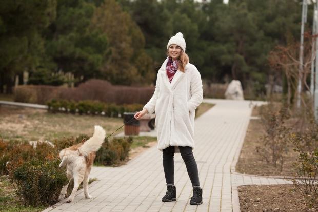 Hund pinkelt in Hecke, Frauchen passt auf - purinarme Ernährung für Hunde bei Harnproblemen
