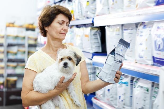 Frau liest Inhaltsangabe von Hundenahrung - die Tierfutterverordnung gilt für die Herstellung