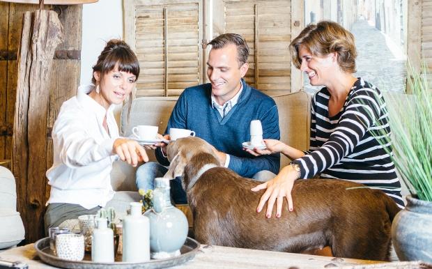 3 Erwachsene kümmern sich gemeinsam um einen Hund