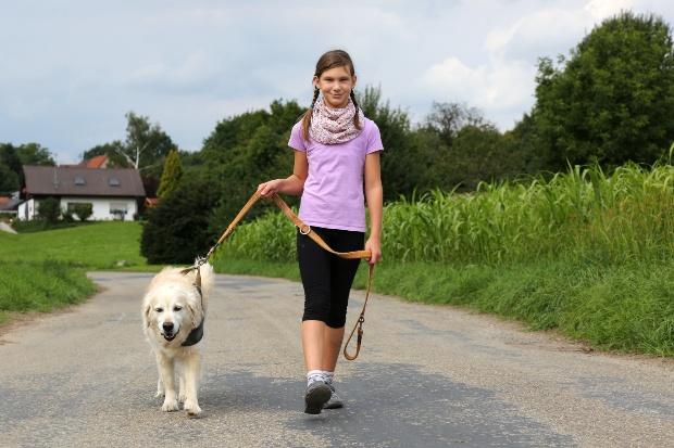 Mädchen führt Hund gassi
