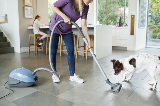Junge Frau saugt die Küche - für einen sauberen Haushalt mit Hund